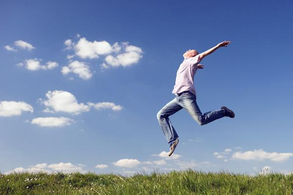Young man is jumping over a green grass